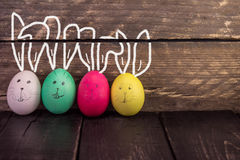 Αστεία χαριτωμένα αυγά Πάσχας στο αγροτικό ξύλινο υπόβαθρο Στοκ Φωτογραφίες