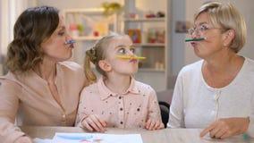 Αστεία multigeneration θηλυκά που κρατούν τα μολύβια χρώματος μεταξύ της μύτη απόθεμα βίντεο