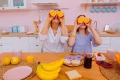 Αστείες αδελφές που τρώνε τα φρούτα μετά από γλυκά doughnuts και τα γλυκά στοκ φωτογραφία