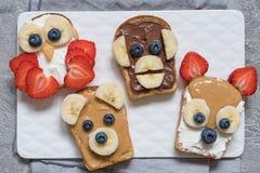 Αστείες ζωικές φρυγανιές προσώπων με την μπανάνα, τη φράουλα και το βακκίνιο Στοκ Εικόνες