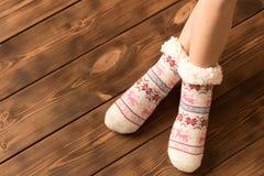 Αστείες θερμές κάλτσες στα πόδια του μικρού κοριτσιού στοκ εικόνες