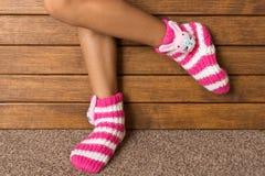 Αστείες ρόδινες κάλτσες στα πόδια ενός μικρού κοριτσιού στοκ φωτογραφία