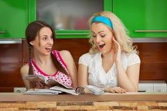Αστείες φίλες που κοιτάζουν βιαστικά τα περιοδικά στην κουζίνα στοκ φωτογραφίες με δικαίωμα ελεύθερης χρήσης