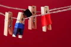 Αστείοι χαρακτήρες και σκοινί για άπλωμα γόμφων Άνδρας στο κοστούμι, κόκκινο φόρεμα γυναικών ξύλινη μακρο άποψη clothespins, ρηχό Στοκ φωτογραφίες με δικαίωμα ελεύθερης χρήσης