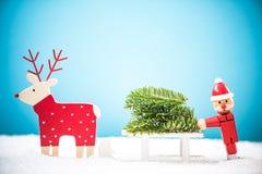 Αστείοι Santa και ο τάρανδος φέρνουν το χριστουγεννιάτικο δέντρο στο χιόνι Στοκ φωτογραφίες με δικαίωμα ελεύθερης χρήσης