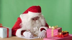 Αστείος Άγιος Βασίλης γράφει μια επιστολή, εξετάζει τη κάμερα και τα κύματα το χέρι του, σημάδι χαιρετισμών, chromakey στο υπόβαθ απόθεμα βίντεο