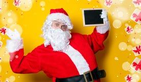 Αστείος Άγιος Βασίλης που κρατά το μαύρο πίνακα Στοκ εικόνα με δικαίωμα ελεύθερης χρήσης