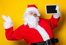 Αστείος Άγιος Βασίλης που κρατά το μαύρο πίνακα Στοκ Φωτογραφία