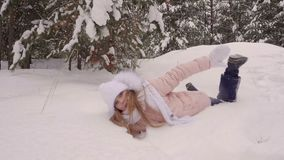Αστείος άσπρος περίπατος κοριτσιών από τη χιονώδη πτώση χορού ANS ξύλων δέντρων πεύκων στο άσπρο χιόνι φιλμ μικρού μήκους
