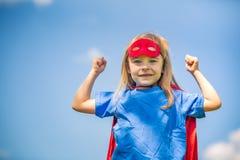 Αστείος έξοχος ήρωας δύναμης μικρών κοριτσιών παίζοντας Στοκ Φωτογραφία