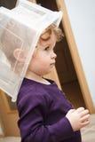 Αστείος λίγο μικρό παιδί που παίζει στο σπίτι με το πλαστικό κιβώτιο Στοκ φωτογραφία με δικαίωμα ελεύθερης χρήσης