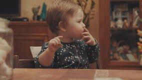 Αστείος λίγο μωρό που τρώει το μπισκότο και που κυματίζει τα χέρια της απόθεμα βίντεο