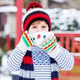 Αστείος λίγο παιδί που κρατά το μεγάλο φλυτζάνι με snowflakes και το καυτό choco Στοκ Φωτογραφίες