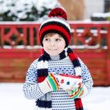 Αστείος λίγο παιδί που κρατά το μεγάλο φλυτζάνι με snowflakes και το καυτό choco Στοκ φωτογραφίες με δικαίωμα ελεύθερης χρήσης