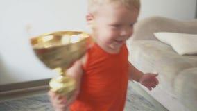 Αστείος αθλητικός τύπος αγοράκι παιδί με ένα βραβείο Το μεγάλο φλυτζάνι Επιτυχία και έννοια νικητών απόθεμα βίντεο