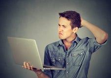 Αστείος ανίδεος τύπος που έχει τα προβλήματα με το lap-top Περίπλοκη τεχνολογία Στοκ Εικόνα