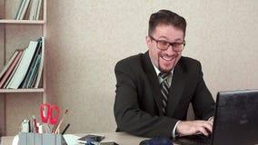 Αστείος διευθυντής γραφείων, μήνυμα δακτυλογράφησης διασκέδασης στο lap-top Είναι στον εργασιακό χώρο απόθεμα βίντεο