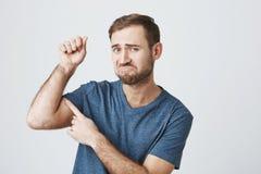 Αστείος δυσαρεστημένος γενειοφόρος τύπος που φορά τα περιστασιακά ενδύματα που αυξάνουν το βραχίονα με την αντλημένη πυγμή, που τ στοκ φωτογραφίες