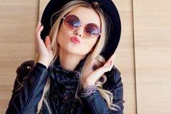 Αστείος και όμορφος ξανθός στα γυαλιά ήλιων και ένα καπέλο Καθιερώνον τη μόδα πορτρέτο κοριτσιών υπαίθριο Φίλημα σας Στοκ Φωτογραφία
