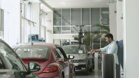 Αστείος μελαμψός τύπος που χορεύει κοντά στο αυτοκίνητο στην αίθουσα εκθέσεως αυτοκινήτων απόθεμα βίντεο
