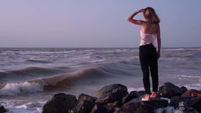 Αστείος ξανθός σε μια μπλούζα στέκεται στους βράχους στη θάλασσα, παίρνει ψεκασμένη από τα κύματα φιλμ μικρού μήκους