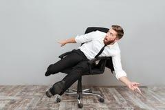 Αστείος τρελλός επιχειρηματίας που έχει τη διασκέδαση καθμένος στην καρέκλα γραφείων Στοκ Εικόνα