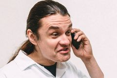 Αστείος τρελλός νεαρός άνδρας που φωνάζει στο τηλέφωνο, την έκφραση και το συναισθηματικό πορτρέτο Στοκ Φωτογραφίες