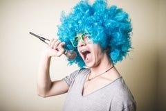 Αστείος τύπος με το μπλε τραγούδι περουκών Στοκ Φωτογραφίες