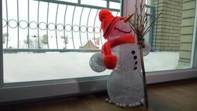 Αστείος χειροποίητος χιονάνθρωπος παιχνιδιών ενάντια στη χιονοθύελλα πίσω από την πόρτα γυαλιού 4k πυροβολισμός φιλμ μικρού μήκους