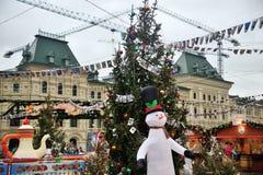 Αστείος χιονάνθρωπος στο έλατο Χριστουγέννων υποβάθρου σε ένα λούνα παρκ Στοκ φωτογραφία με δικαίωμα ελεύθερης χρήσης