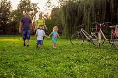 Αστείος χρόνος - ευτυχή παιδιά που περπατούν με τους γονείς στο πάρκο στοκ εικόνες με δικαίωμα ελεύθερης χρήσης