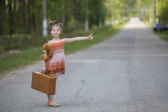 Αστείος hitchhiker μικρών κοριτσιών με μια βαλίτσα και μια teddy αρκούδα Ταξίδι Στοκ εικόνες με δικαίωμα ελεύθερης χρήσης