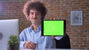 Αστείος nerdy εργαζόμενος γραφείων με τη σγουρή τρίχα όγκου που δείχνει την ταμπλέτα με το κλειδί χρώματος στη κάμερα και που χαμ φιλμ μικρού μήκους