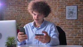 Αστείος nerdy εργαζόμενος γραφείων που πληρώνει τους λογαριασμούς στο τηλέφωνο με την πιστωτική κάρτα, τη συνεδρίαση και τις αγορ φιλμ μικρού μήκους