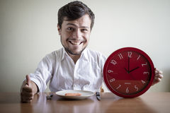 Αστείο άτομο μαριονετών με το άσπρο πουκάμισο που κρατά το κόκκινο ρολόι Στοκ Εικόνες