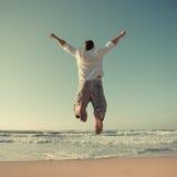 Αστείο άτομο που πηδά στην παραλία στοκ φωτογραφίες