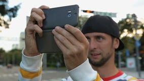 Αστείο άτομο στο βίντεο μαγνητοσκόπησης ΚΑΠ στο smartphone στην οδό, σύγχρονος ιματισμός απόθεμα βίντεο