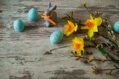 Αστείο λαγουδάκι Πάσχας σε ένα ξύλινο υπόβαθρο whigt και κεριά υπό μορφή αυγών Πάσχας Στοκ εικόνα με δικαίωμα ελεύθερης χρήσης