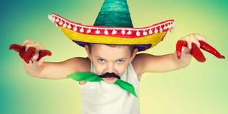 Αστείο αγόρι με ένα πλαστό mustache και στα μεξικάνικα παιχνίδια σομπρέρο στοκ φωτογραφία
