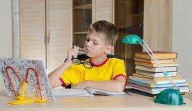 Αστείο αγόρι με τα γυαλιά που κάνουν την εργασία εκμάθηση δυσκολιών παιδ& Αγόρι που έχει τα προβλήματα με την εργασία του η εκπαί Στοκ Εικόνες