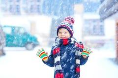 Αστείο αγόρι παιδάκι στα ζωηρόχρωμα ενδύματα που παίζει υπαίθρια κατά τη διάρκεια των ισχυρών χιονοπτώσεων Στοκ Φωτογραφία