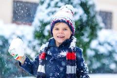 Αστείο αγόρι παιδάκι στα ζωηρόχρωμα ενδύματα που παίζει υπαίθρια κατά τη διάρκεια των ισχυρών χιονοπτώσεων Στοκ εικόνα με δικαίωμα ελεύθερης χρήσης