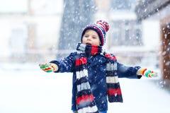 Αστείο αγόρι παιδάκι στα ζωηρόχρωμα ενδύματα που παίζει υπαίθρια κατά τη διάρκεια των ισχυρών χιονοπτώσεων Στοκ Εικόνες