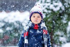 Αστείο αγόρι παιδάκι στα ζωηρόχρωμα ενδύματα που παίζει υπαίθρια κατά τη διάρκεια των ισχυρών χιονοπτώσεων Στοκ φωτογραφίες με δικαίωμα ελεύθερης χρήσης
