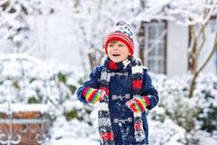 Αστείο αγόρι παιδάκι στα ζωηρόχρωμα ενδύματα που παίζει υπαίθρια κατά τη διάρκεια των ισχυρών χιονοπτώσεων Στοκ εικόνες με δικαίωμα ελεύθερης χρήσης