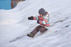 Αστείο αγόρι παιδάκι στα ζωηρόχρωμα ενδύματα που παίζει υπαίθρια το χειμώνα τις κρύες χιονώδεις ημέρες Ευτυχές παιδί που έχει τη  Στοκ Εικόνες