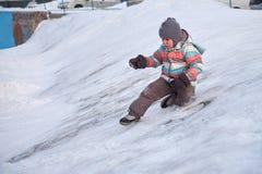 Αστείο αγόρι παιδάκι στα ζωηρόχρωμα ενδύματα που παίζει υπαίθρια το χειμώνα τις κρύες χιονώδεις ημέρες Ευτυχές παιδί που έχει τη  Στοκ εικόνα με δικαίωμα ελεύθερης χρήσης