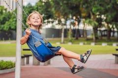 Αστείο αγόρι παιδιών που έχει τη διασκέδαση με την ταλάντευση αλυσίδων στην υπαίθρια παιδική χαρά παιδί που ταλαντεύεται τη θερμή Στοκ Εικόνες