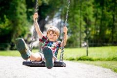 Αστείο αγόρι παιδιών που έχει τη διασκέδαση με την ταλάντευση αλυσίδων στην υπαίθρια παιδική χαρά ενώ όντας υγρός καταβρεγμένος μ Στοκ εικόνες με δικαίωμα ελεύθερης χρήσης