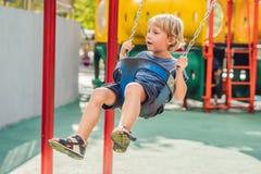Αστείο αγόρι παιδιών που έχει τη διασκέδαση με την ταλάντευση αλυσίδων στην υπαίθρια παιδική χαρά Στοκ Εικόνες